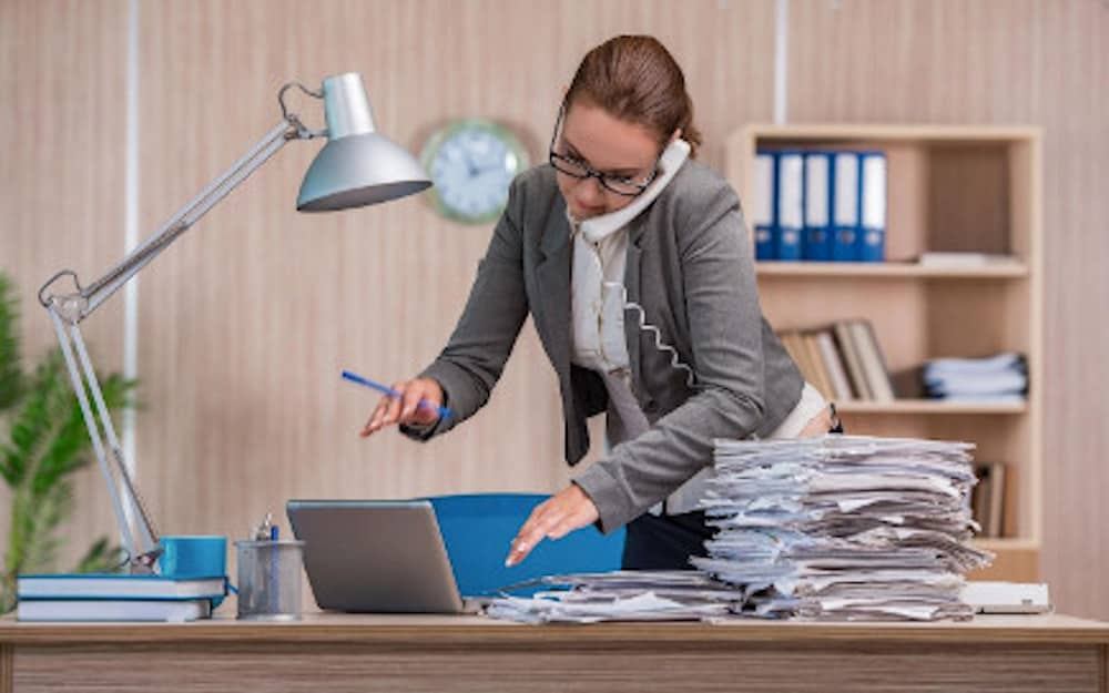 woman bust at working working on pile of papers and talking to someone over the phone