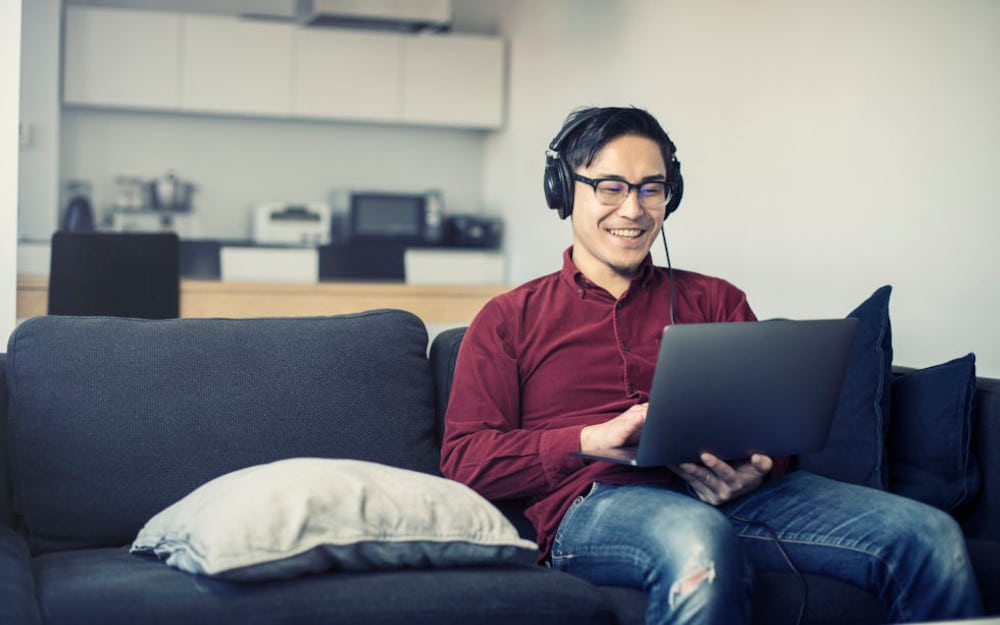 guy on a couch with laptop and headset